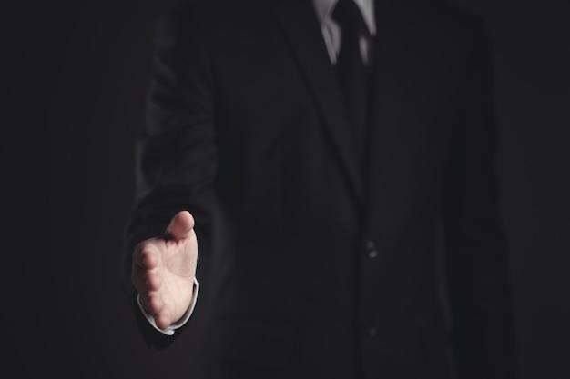 Бизнесмен в черном костюме с открытой ладонью готов к сделке и рукопожатие на черном
