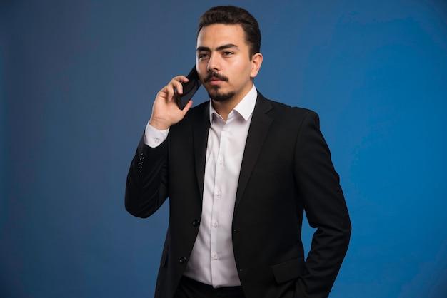 Бизнесмен в черном костюме разговаривает по телефону.
