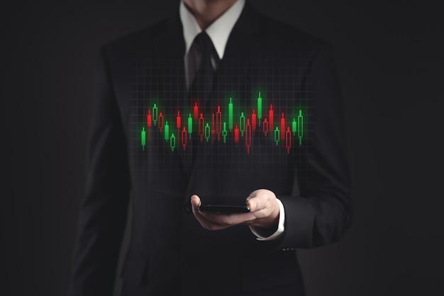 投資のためのスマートフォンの計画を使用して黒いスーツのビジネスマン