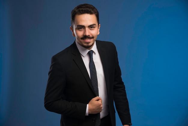 Бизнесмен в черном костюме с галстуком позирует позитивно.