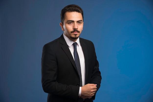 Бизнесмен в черном костюме с галстуком позирует.