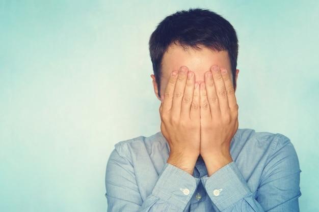 Бизнесмен в голубой рубашке, закрыл лицо руками на синем фоне. мужчина прячет слезы.