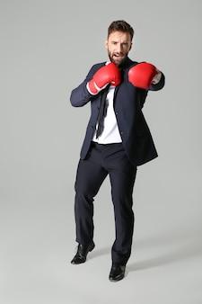 灰色の表面にボクシンググローブのビジネスマン
