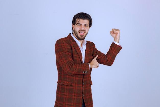 Бизнесмен в коричневой куртке показывает кулаки и указывает на свой успех и силу.