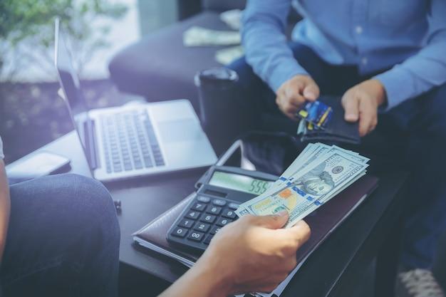 비즈니스 회의에서 사업가 계산 및 비즈니스 파트너와 협상 후 돈을 지불