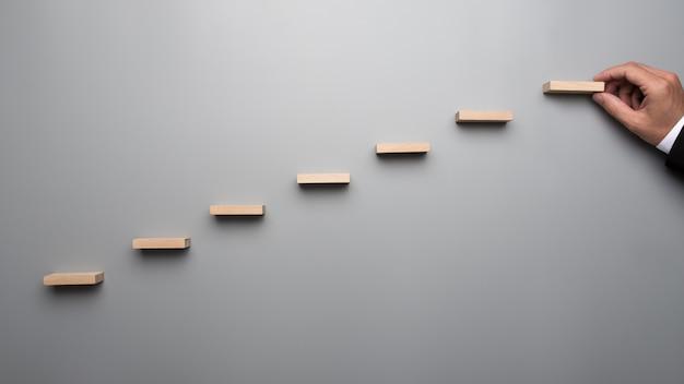 ビジネススーツのビジネスマンは、灰色の背景に成功のグラフやはしごを構築します。