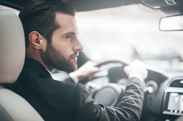 차에 사업가입니다. 차를 운전하는 동안 오른쪽을 바라보는 젊은 잘생긴 남자의 뒷모습