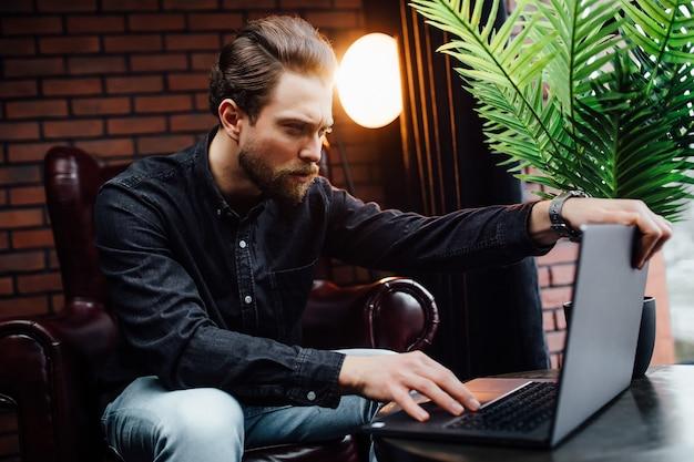 コーヒーを飲みながら、カフェでノートパソコンで仕事をしているカジュアルな服装のビジネスマン。