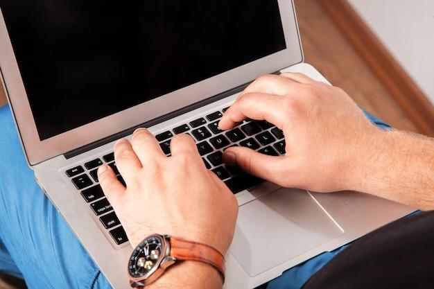 ノートパソコンでテキストを入力するカジュアルな服のビジネスマン労働者