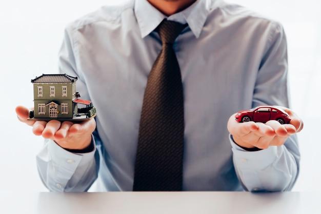 Бизнесмен в дилемме планирования выбора между тратой дома или автомобиля