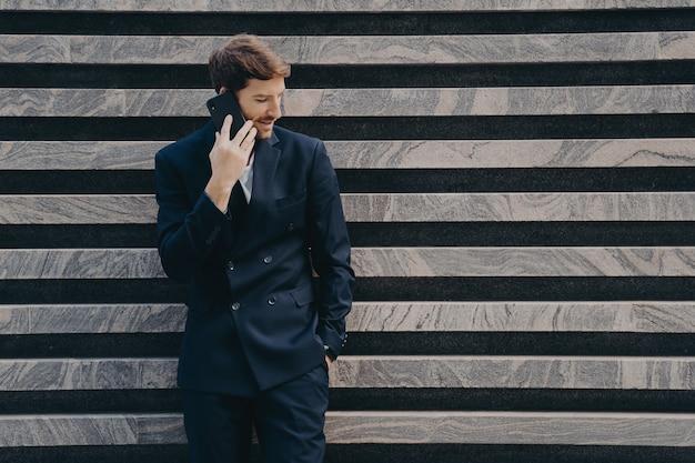 Бизнесмен в элегантных черных телефонах одежды, чтобы партнер сосредоточился, держит смартфон
