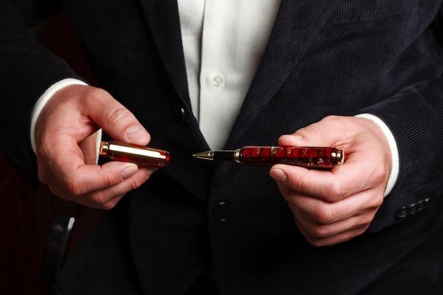 エレガントなスーツのビジネスマンが彼の手でペンを保持しています。