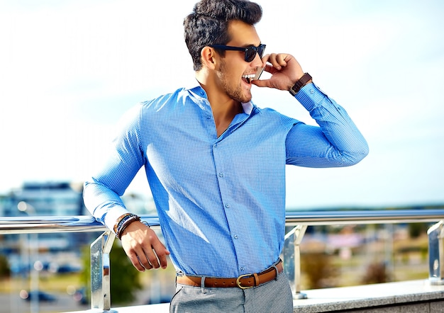 Бизнесмен в формальной одежде и солнцезащитные очки, используя свой телефон