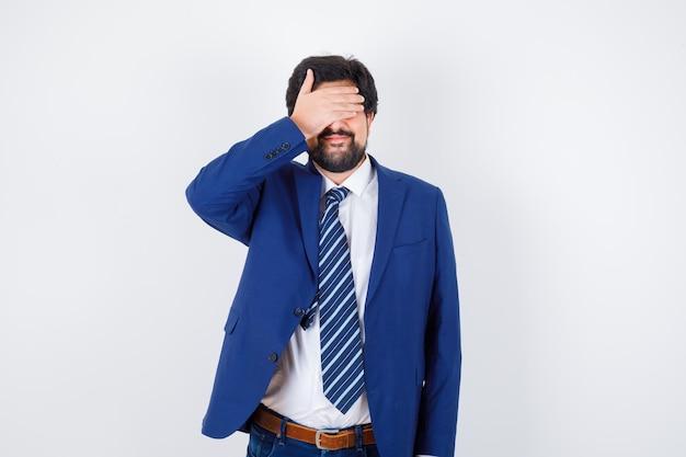 Бизнесмен в официальном костюме, закрывающий глаза рукой и серьезный вид спереди.
