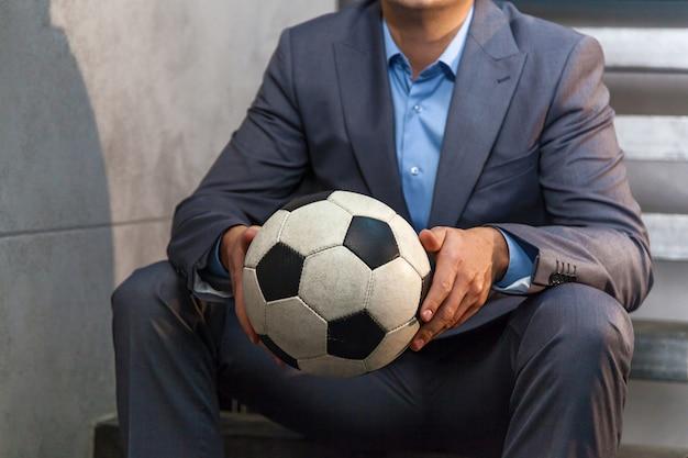 フォーマルなスーツを着たビジネスマンがサッカーボールを手に持っています。