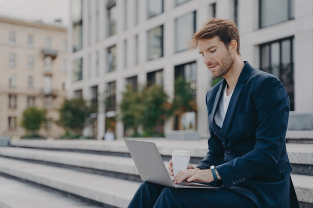 Бизнесмен в строгом костюме читает новости через портативный компьютер, работает онлайн, пьет кофе на вынос