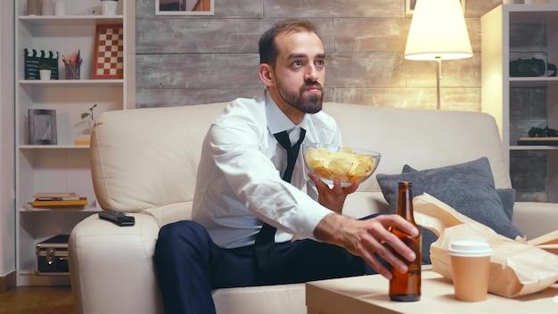 Бизнесмен в формальной одежде, сидя на диване, ест чипсы во время просмотра телевизора.
