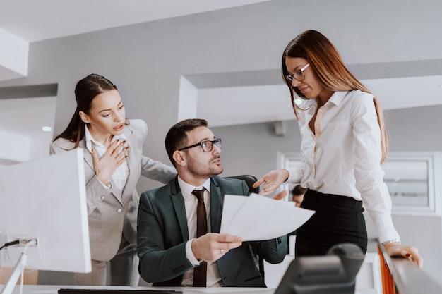 Бизнесмен в официально носке разговаривая с его женскими коллегами о документах пока сидящ в современном офисе.