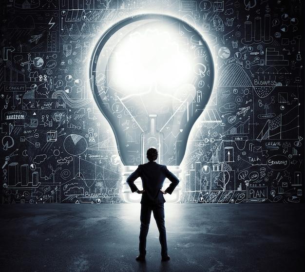 電球の形をした大きなドアの前にいるビジネスマン