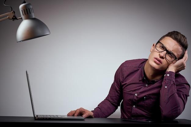 Бизнесмен в очках и рубашке сидит за столом с открытыми ноутбуками мобильный телефон coffee space. фото высокого качества