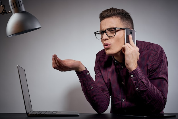 Бизнесмен в очках и рубашке сидит за столом с открытыми ноутбуками