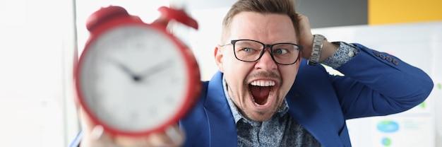 안경을 쓴 사업가가 빨간 알람 시계를 손에 들고 업무 시간을 외치고 있다