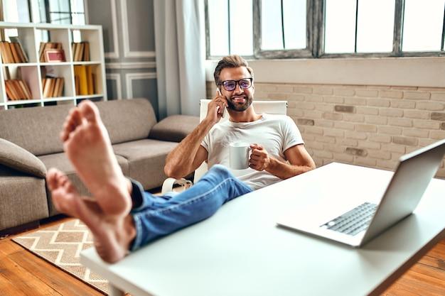 コーヒーのマグカップを持って眼鏡をかけているビジネスマンは、テーブルに足を置いて座っている間、ラップトップで動作します。フリーランス、自宅で仕事。