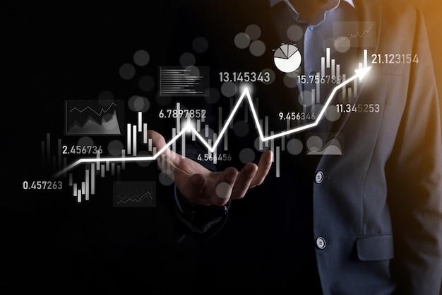 손에 든 사업가는 은행 비즈니스 재무 그래프를 잡고 주식 시장 투자 포인트, 경제 성장 및 투자자 개념에 투자합니다. 가상 주식 시장 차트 분석, 사용 기술로 분석 프리미엄 사진