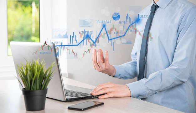 手持ちのビジネスマンは、銀行業務の財務グラフを保持し、株式市場の投資ポイント、経済成長、投資家の概念に投資します。分析仮想株式市場チャート、使用技術による分析