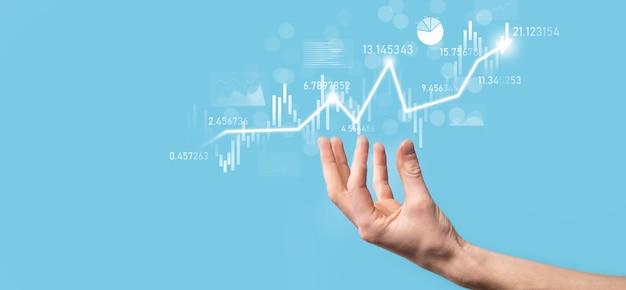 손에 든 사업가는 은행 비즈니스 재무 그래프를 잡고 주식 시장 투자 포인트, 경제 성장 및 투자자 개념에 투자합니다. 가상 주식 시장 차트를 분석하고 기술을 사용하여 분석합니다.