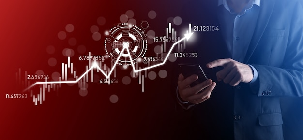 手にビジネスマンは、銀行業務の財務グラフを保持し、株式市場の投資ポイント、経済成長、投資家の概念に投資します。分析仮想株式市場チャート、使用技術による分析