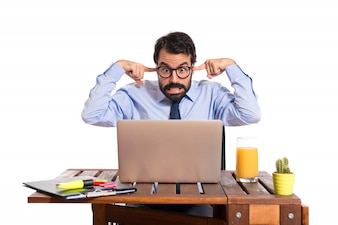 Businessman in his office covering his ears