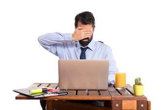 Businessman in his office covering his eyes