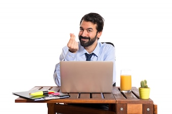 Businessman in his office doing money gesture