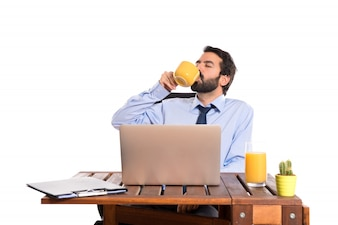 Businessman in his office drinking coffee