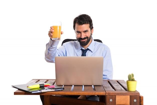 オレンジジュースを飲む彼のオフィスのビジネスマン