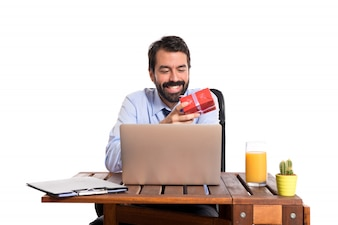 Businessman in his office giving a gift