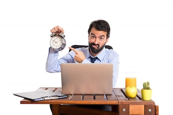 Businessman in his office holding a clock
