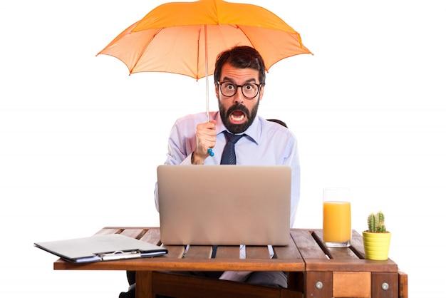 Бизнесмен в своем офисе с зонтиком
