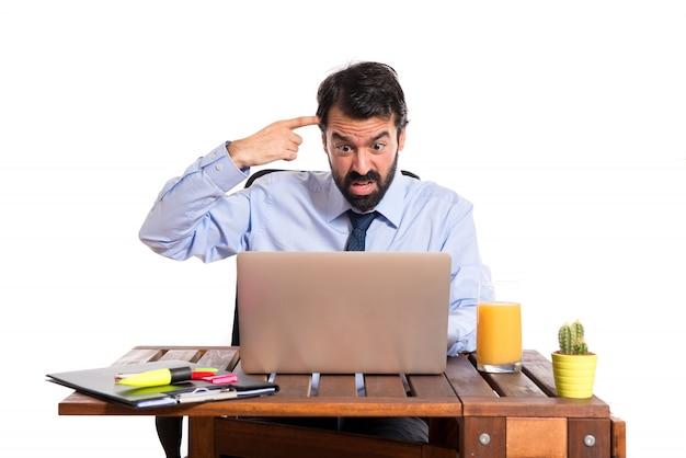 狂ったジェスチャーを作る彼のオフィスのビジネスマン