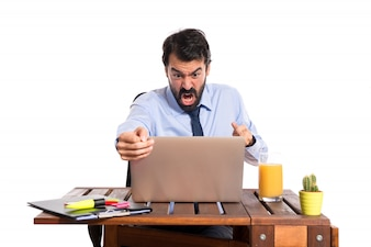 Businessman in his office making horn gesture