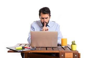 Businessman in his office making silence gesture