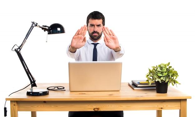 Бизнесмен в своем офисе делает знак остановки
