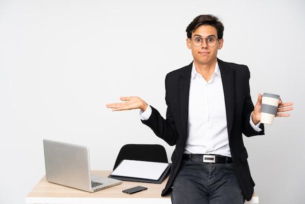 混乱した表情で疑問を持つ孤立した白い壁の上の彼のオフィスのビジネスマン