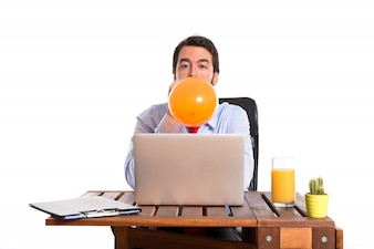 Businessman in his office playing with balloon