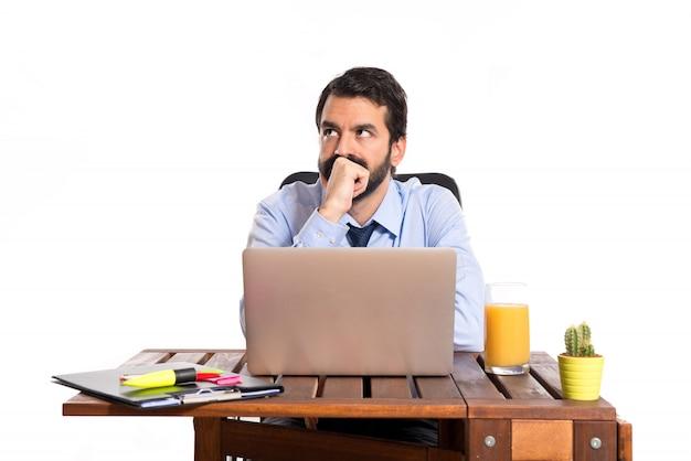 白い背景の上で考えている彼のオフィスのビジネスマン