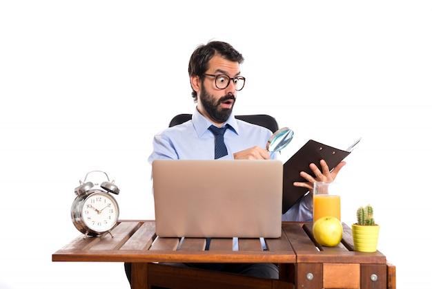 彼のオフィスでは虫めがねのビジネスマン