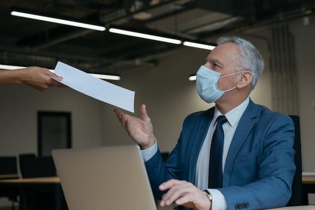 종이 문서 또는 재무 보고서를받는 의료 마스크에서 사업가. 사회적 거리 개념