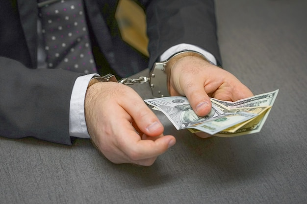 賄賂を保持している手錠でオフィスにいるビジネスマン。セレクティブフォーカス