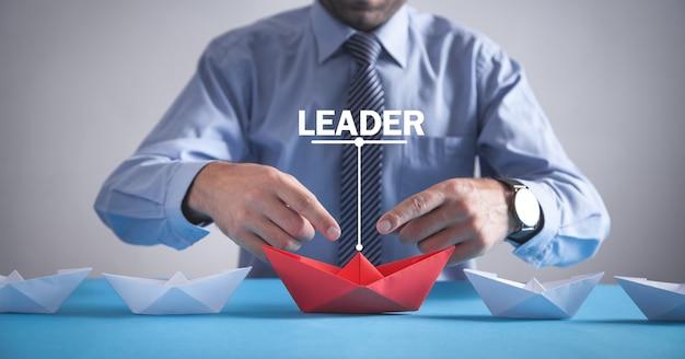 사무실에서 사업가입니다. 흰색 보트와 빨간 종이 접기 종이 보트. 비즈니스, 리더십